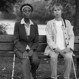Actors Margo Cargill and Alex Bulmer sit on park bench, each with white stick, in Awake